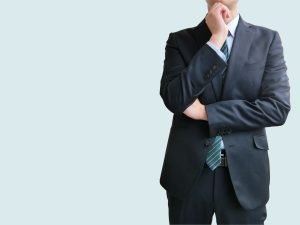 考え事をするスーツの男性